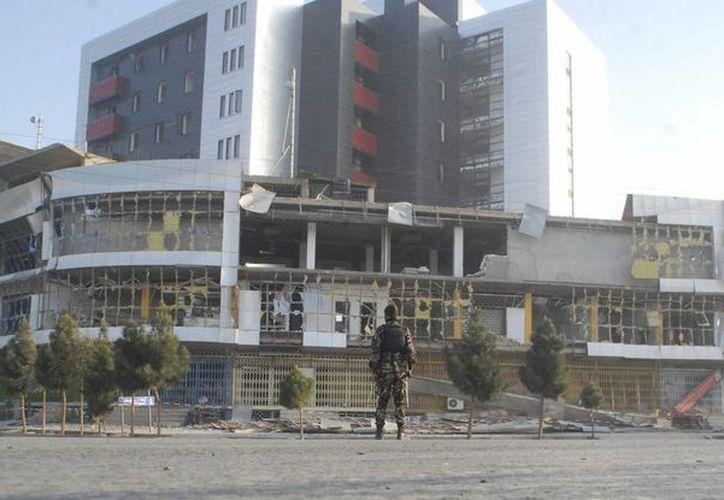 Un miembro de las fuerzas de seguridad afganas inspecciona el lugar  tras la detonación de un camión bomba y el posterior asalto al consulado de Alemania en Mazar-e-Sharif, en el norte de Afganistán. (EFE/Mutalib Sultani)