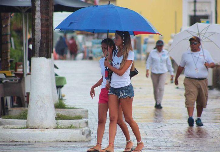 Pocos turistas se atrevieron a salir al centro de la ciudad, el cual lució desolado por momentos. Aunque ayer la lluvia no fue intensa, prestadores de servicios esperan que la situación mejore hoy. (Gustavo Villegas/SIPSE)