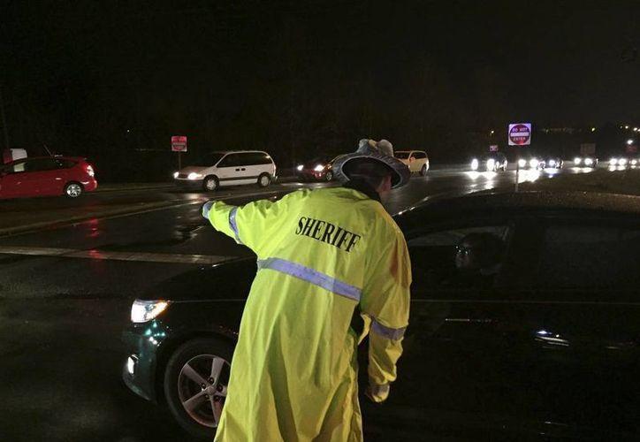 En esta fotografía proporcionada por ABC11, un agente del departamento policial del condado de Alamance dirige el tráfico cerca de la salida 154 en la interestatal 40 después de múltiples accidentes. (Agencias)