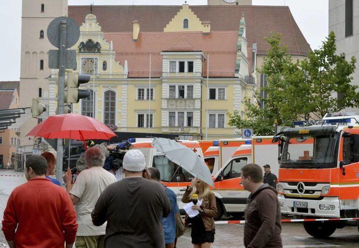Varios vehículos de emergencias y un grupo de ciudadanos y periodistas rodean el Ayuntamiento de Ingolstadt, al sur de Alemania. (EFE)