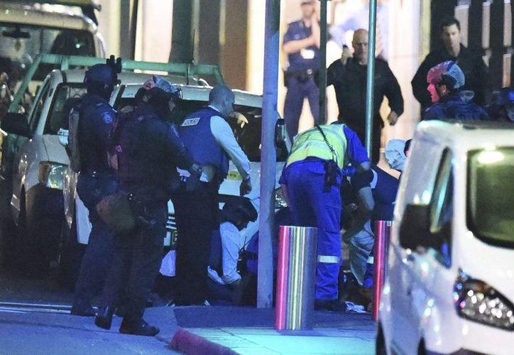 Miembros de los servicios médicos atienden a un herido junto a la cafetería tomada desde primeras horas de la mañana por un hombre armado en Sídney, Australia. (EFE)