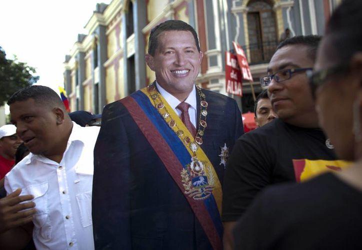 Partidarios de Hugo Chávez cargan una imagen de tamaño natural del gobernante venezolano durante una ceremonia simbólica de la nueva asunción presidencial en Caracas, el 10 de enero de 2013. (Agencias)