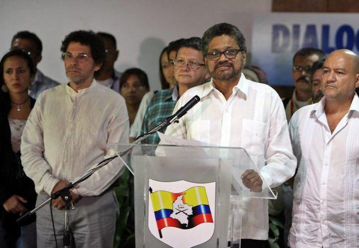 """El segundo jefe de las FARC y líder de los delegados de la guerrilla, Luciano Marín (c), alias """"Iván Márquez"""", junto a varios representantes de la guerrilla en la mesa de negociaciones con el Gobierno colombiano, lee un comunicado, el pasado miércoles 8 de julio de 2015, en el Palacio de Convenciones de La Habana, Cuba. (EFE)"""