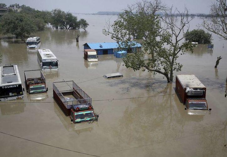Varios vehículos semihundidos tras el desbordamiento del río Yamuna, en Nueva Delhi, la India, hoy, jueves 20 de junio de 2013. (EFE)