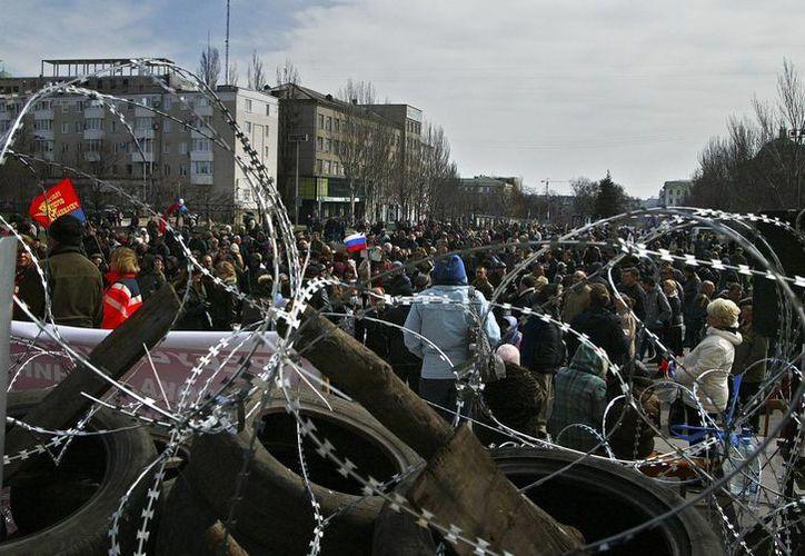 Activistas preparan una barricada en el edificio administrativo de Donetsk, Ucrania. (Agencias)