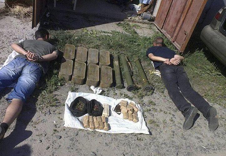 Imagen de dos raficantes de armas detenidos y armas confiscadas en Cherkasy, Ucrania. (Servicio de Seguridad de Ucrania vía AP)