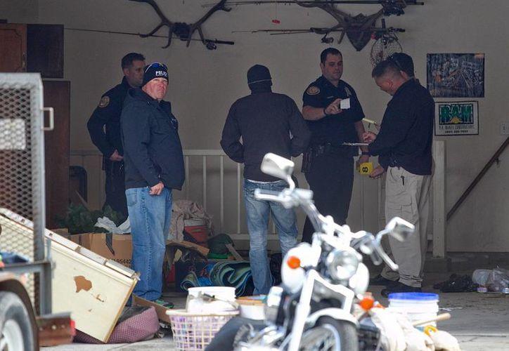 Policías investigan la casa donde fueron encontrados los cadáveres de siete bebés guardados en cajas dentro de un garaje en Utah. (Agencias)