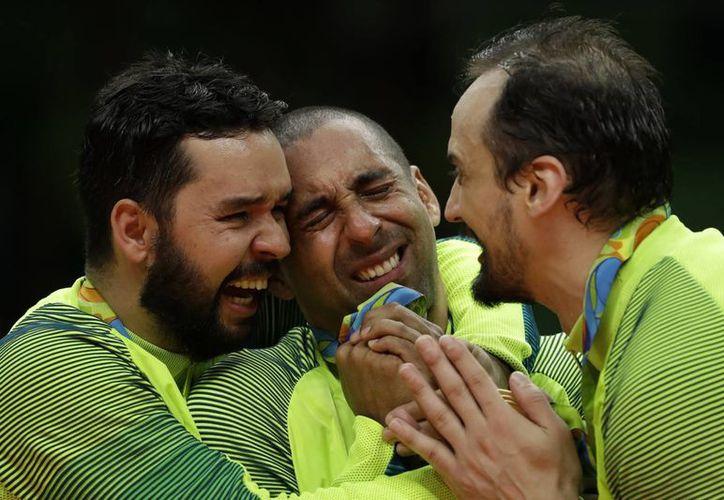 Los brasileños William Arjona, Sergio Dutra Santos y Luiz Felipe Marques en emotivo festejo luego de recibir la medalla de oro del voleibol varonil que se adjudicaron este domingo, en Río 2016. (AP/Matt Rourke)