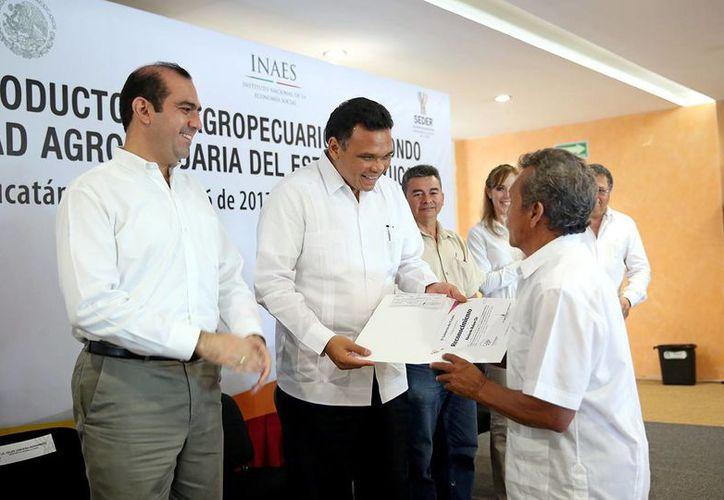 El gobernador Rolando Zapata Bello entrega un cheque a uno de los beneficiarios. (SIPSE)
