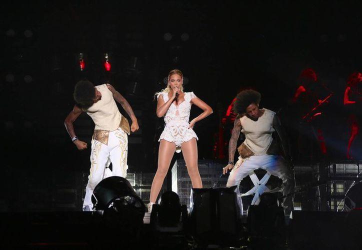 Tras ser derribada, Beyoncé siguió cantando y, al terminar el tema, saludó de mano al impulsivo fanático. (Agencias)