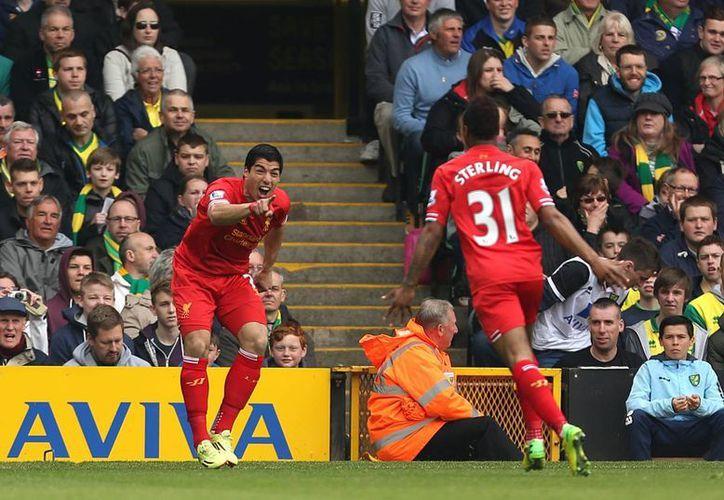 Luis Suárez festeja con su compañero Raheem Sterling el gol que dio el triunfo al Liverpool sobre el Norwich. (AP)