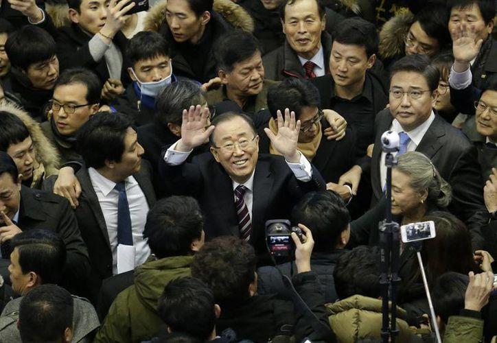 El ex secretario general de la ONU Ban Ki-moon, centro, saluda a sus seguidores en la estación ferroviaria de Seúl, Corea del Sur. (AP/Ahn Young-joon)