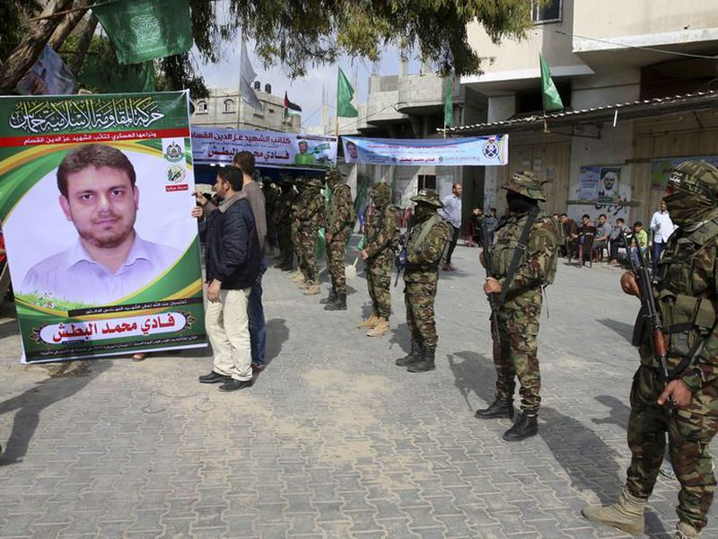Relatives hold a sign next to the soldiers of the Izzedine al-Qassam Brigades, a military wing of Hamas.
