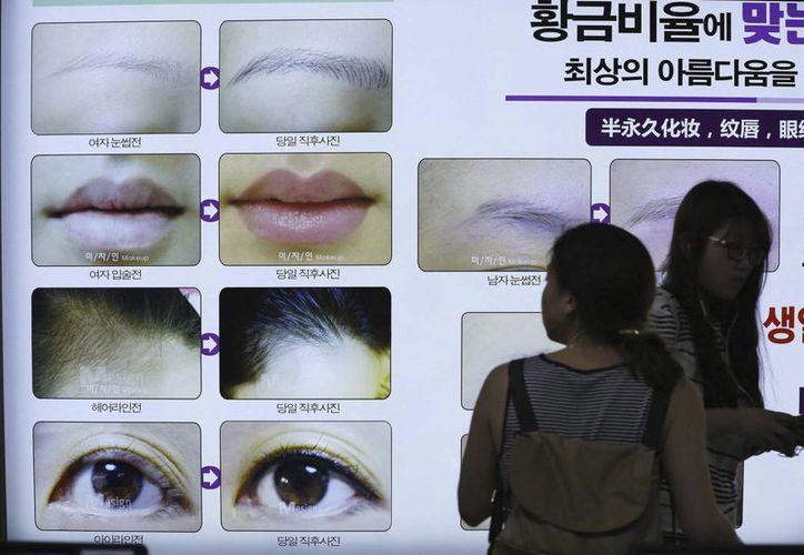 Una mujer observa un cartel que anuncia cambios de imagen en el Metro en Seúl, Corea del Sur, país donde hay más de cuatro mil clínicas de cirugía estética. (EFE)