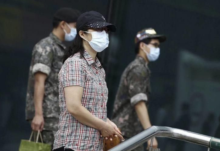Soldados y civiles pasean con mascarillas por las calles de Seúl, Corea del Sur. El coronavirus se cobró otra víctima en Corea del Sur. Hong Kong emite alerta roja para los que viajan a este país. (EFE)