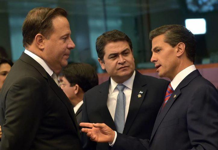 El presidente de México, Enrique Peña Nieto, quien habló sobre la migración en el marco del cierre de la Cumbre del Celac y la Unión Europa, saluda a sus homólogos de Panamá y Honduras, Juan Carlos Valera y Juan Orlando Hernández. (Notimex)