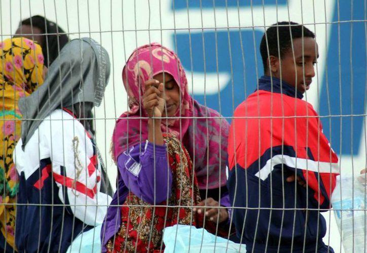 Un grupo de inmigrantes caminan por el puerto de Lampedusa, Italia. (EFE)