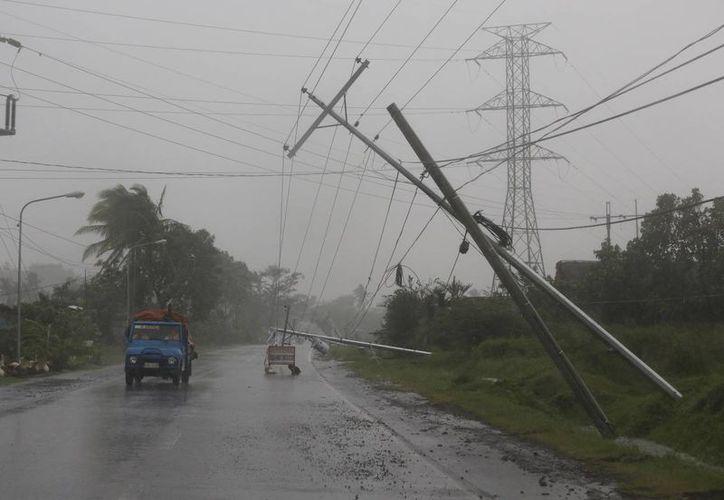 Conductores y transportistas avanzan peligrosamente entre postes eléctricos caídos o a punto de caer debido al lento avance del tifón Hagupit en Camalig, provincia de Albay, en Filipinas. (Foto: AP)