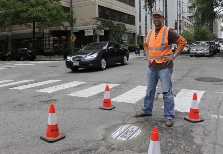 Un bache relleno por el artista de mosaicos Jim Bachor en una calle en Chicago. (Agencias)
