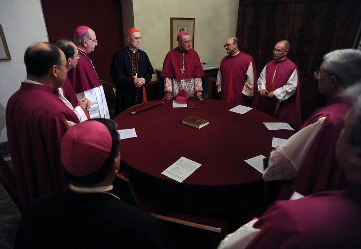 El Cardenal Tarcisio Bertone, Secretario de Estado Vaticano, en el centro a la izquierda con gorro rojo, oficialmente se hace cargo de la sede vacante como Camarlengo. (Agencias)