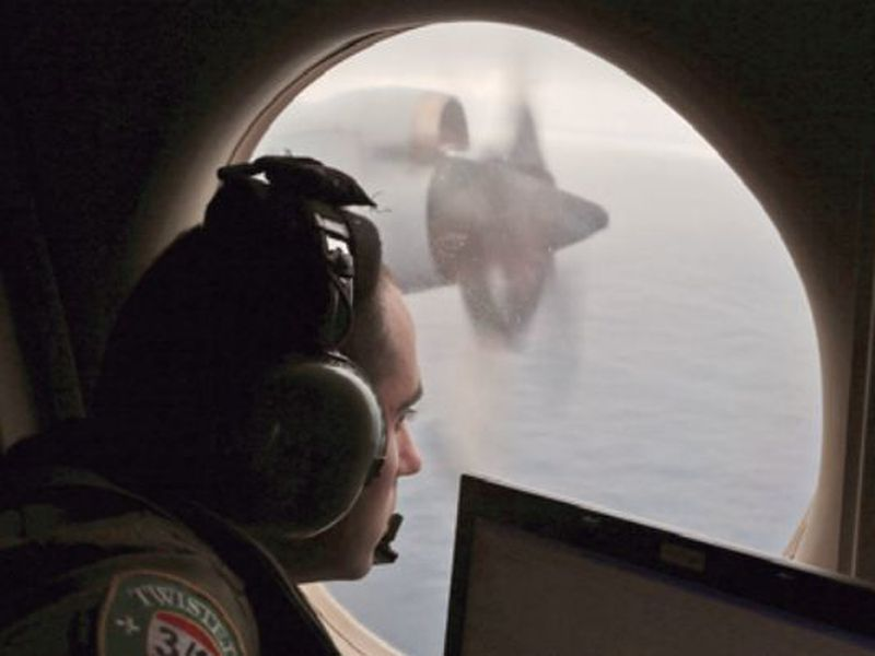 Flight officer Rayan Gharazeddine scans the water in the southern Indian Ocean off Australia from a Royal Australian Air Force AP-3C Orion during a search for the missing Malaysia Airlines Flight MH370. (AP)