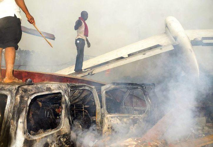 Nigerianos revisan los escombros de un avión comercial con 159 personas a bordo, que se estrelló en un barrio de Lagos. (EFE/Archivo)