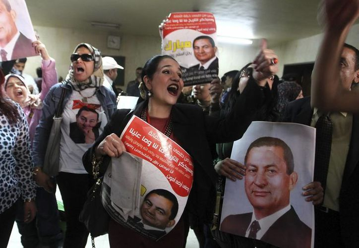 Simpatizantes del expresidente egipcio Hosni Mubarak muestran carteles con su foto durante una protesta en un juzgado de El Cairo, Egipto. (Archivo/EFE)