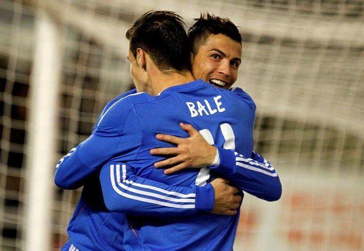 Cristiano Ronaldo genera cifras millonarias al club merengue. En la imagen, el portugués y Gareth Bale festejan una anotación. (AP)