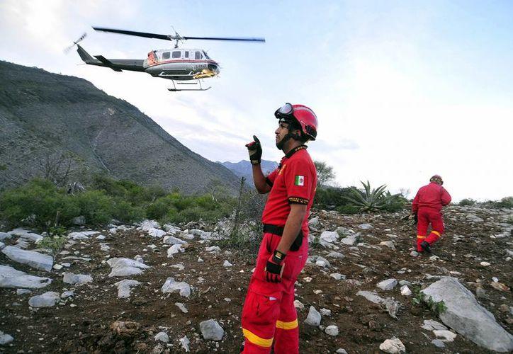 Autoridades federales observan el sitio donde cayó la aeronave donde viajaba la cantante méxico-estadounidense Jenni Rivera. (EFE)