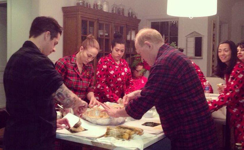 La actriz Jennifer López (i) compartió en Twitter esta foto en la que se ve junto con su familia preparando los tradicionales pasteles puertorriqueños. (EFE)
