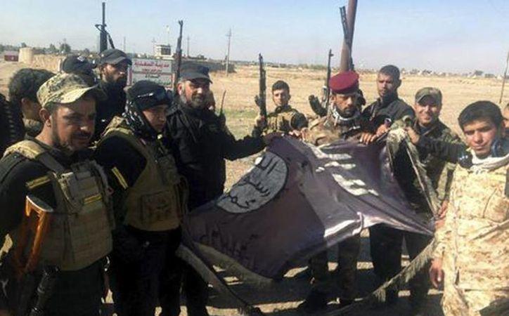 Varios soldados iraquíes sostienen una bandera del Estado Islámico destrozada en Al Saadiya, en la provincia de Diyala, al noreste de Irak. (Excelsior vía EFE)