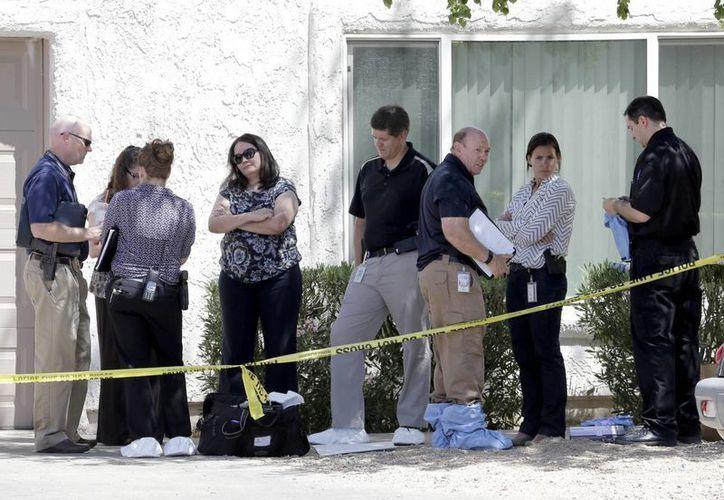 Oficiales de policía permanecen afuera de la casa donde sucedió la tragedia familiar. La madre de los niños fue hospitalizada en estado crítico por tener heridas de arma blanca que se autoinfligió. (Foto AP / Matt York)