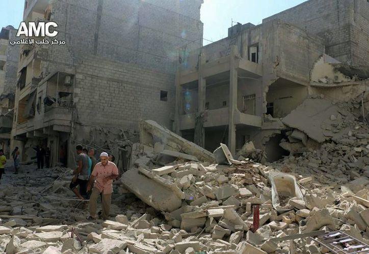 Sirios inspeccionan las casas dañadas por el ataque aéreo que lanzó el gobierno de Siria. (Agencias)