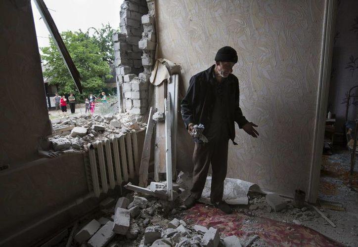 Sorvar Yasinov, un civil de 76 años, contempla desde dentro su casa destruida por un ataque a las afueras de Slovyansk, Ucrania. (Foto: AP)