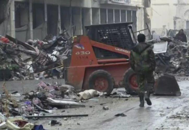 Soldados sirios que caminan entre edificios dañados por la guerra en la ciudad vieja de Alepo. (AP)