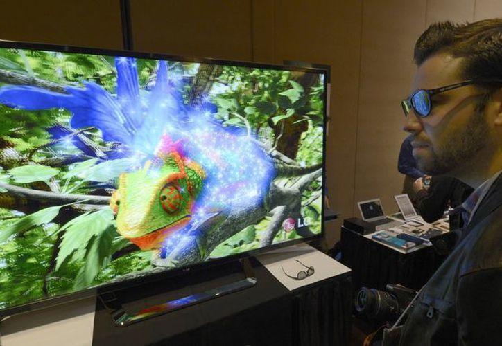 Un asistente observa un nuevo modelo de televisor 3D promocionado por LG, durante la víspera de la apertura de la feria CES, en Las Vegas. (EFE)