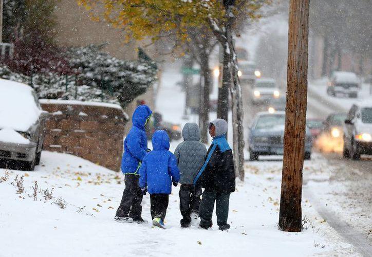 Un grupo de niños de Minnesota caminan hacia el colegio durante una nevada. (Agencias)