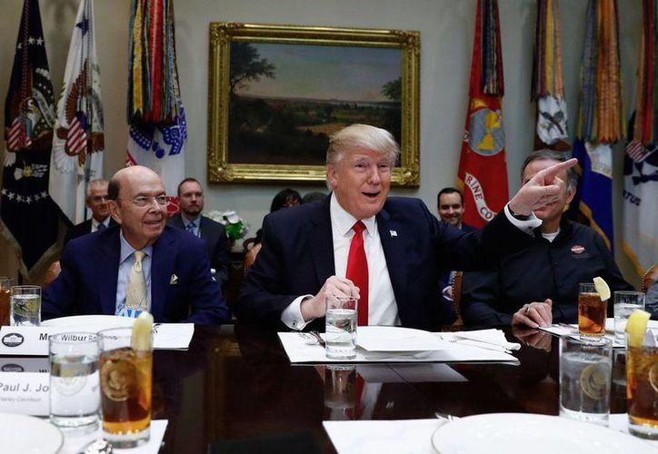 Donald Trump, flanqueado por el nomiado secretario de Comercio, Wilbur Ross, izq. y el CEO de Harley Davidson, Matt Levatich, habla con legisladores en el salón Roosevelt de la Casa Blanca, jueves 2 de febrero de 2017. (AP/Carolyn Kaster)