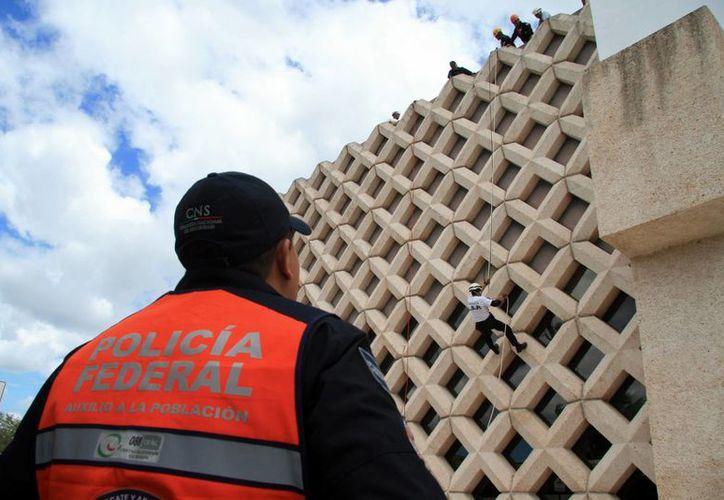 En la fachada poniente del Centro de Convenciones, elementos de la Policía Federal y Bomberos de la SSP realizaron prácticas de rapel, para fortalecer la experiencia de los agentes en el descenso en caso de apoyo. (Milenio Novedades)