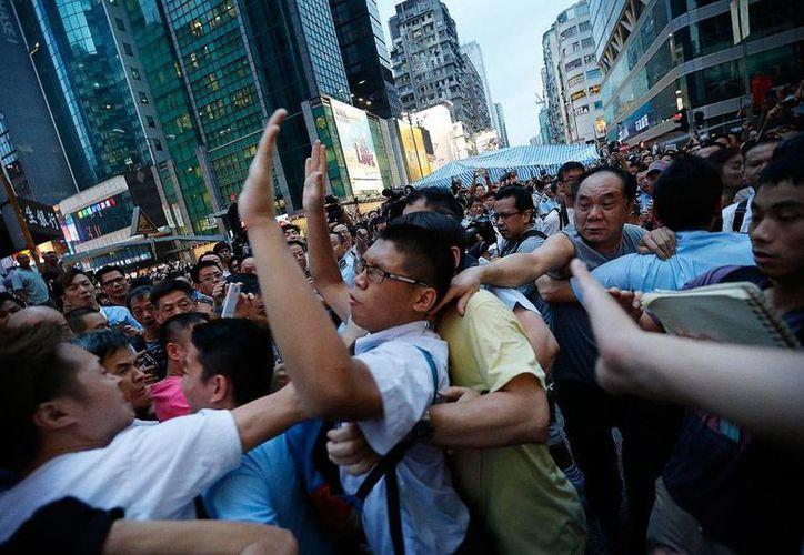 'Hartos' de la protesta de los estudiantes y ciudadanos, vecinos de Hong Kong salieron a la calle para 'frenar' a loa manifestantes. Hubo roces, pero no se reportaron heridos. (AP)