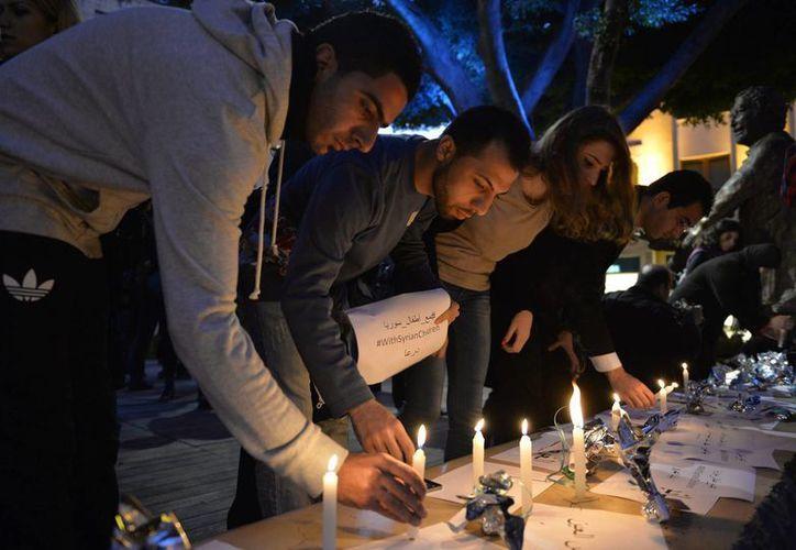 Activistas libaneses y sirios participan en una vigilia de conmemoración del tercer aniversario del comienzo del conflicto sirio contra el régimen del presidente de Siria, Bachar Al Asad, frente a la estatua del periodista franco libanés Samir Kassir, asesinado en Beirut hace nueve años. (EFE/Archivo)