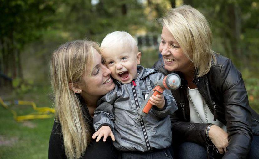 Emelie Eriksson (izq) juega con su hijo Albin bajo la mirada de su madre Marie, en Berghamra, Suecia. Eriksson dio a luz luego de que su madre le donó su útero. (AP Photo/ Niklas Larsson)