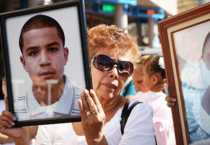 En la imagen, la madre del adolescente fallecido carga una foto de José Antonio Elena Rodríguez, en Sonora. (contrainjerencia.com)