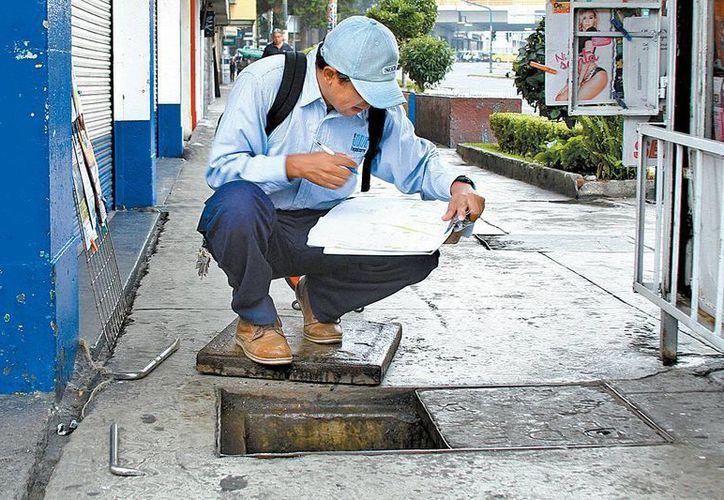 Un técnico de una empresa filial de Teléfonos de México revisa un registro del cableado subterráneo en el D.F. (Milenio Novedades)
