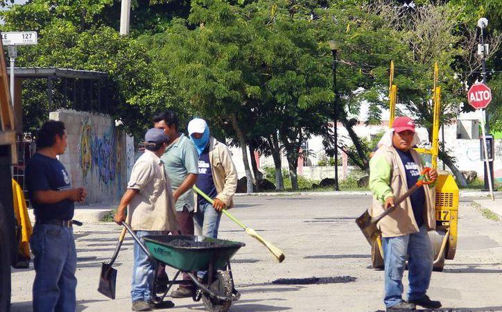 Hay calles con más de 30 años y formarán parte del plan que realizarán cuando determinen hacer un programa de renivelaciones totales. Imagen de un grupo de empleados del municipio en trabajos de bacheo. (Milenio Novedades)