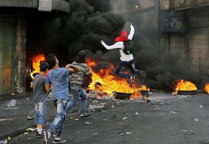 Manifestantes palestinos lanzan piedras hacia soldados israelíes durante un día más de enfrentamientos registrados en la ciudad cisjordana de Hebrón. (EFE)