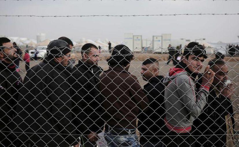 La ONU detiene paulatinamente las operaciones de ayuda a los vecindarios del este de Mosul, retomadas del grupo del Estado islámico, por razones de seguridad. Imagen de contexto de un grupo de hombres detrás de una malla metálica en un campo para desplazados de Mosul. (AP Photo / Bram Janssen).