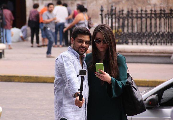 Turistas nacionales hablan de su visita a Mérida en las redes sociales. En la imagen, dos visitantes se toman una selfie teniendo como fondo la Catedral de Mérida. (Jorge Acosta/SIPSE)
