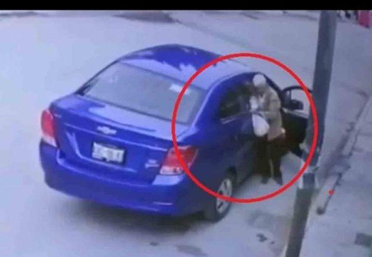 El conductor del vehículo arranca de prisa, con la puerta del copiloto abierta y dejando al hombre en la calle. (Captura de pantalla)