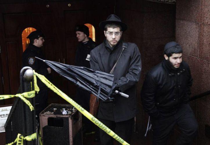 Un miembro de la comunidad Lubavich, centro, sale de la sede de la secta jasídica Jabad Lubavitch entre agentes de policía, en Brooklyn, Nueva York. (Agencias)